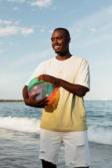 Hombre sonriente de tiro medio sosteniendo la bola