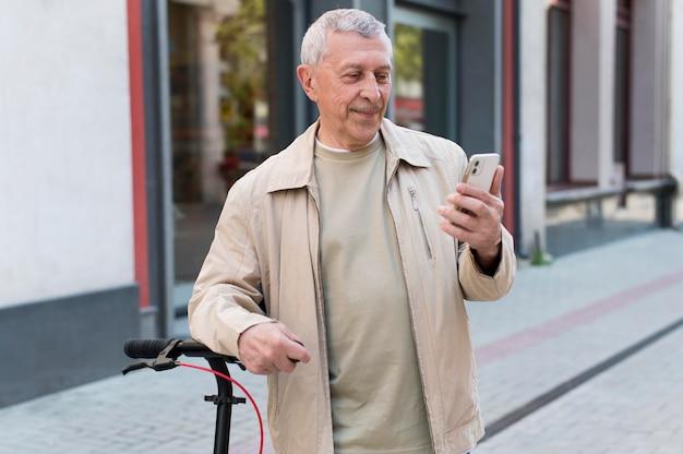Hombre sonriente de tiro medio sujetando el teléfono
