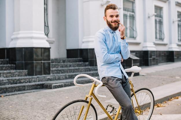 Hombre sonriente tocando el bigote cerca de la bicicleta