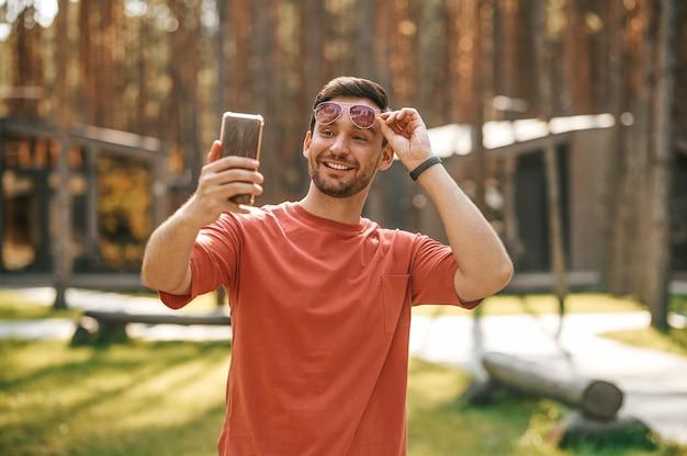 Hombre sonriente tocando vasos tomando selfie