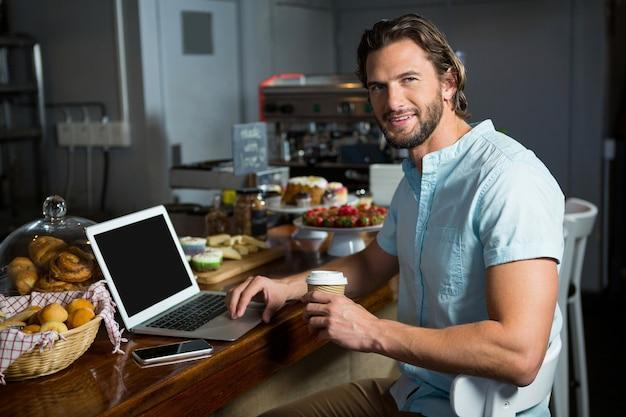 Hombre sonriente tomando café mientras usa la computadora portátil en el mostrador