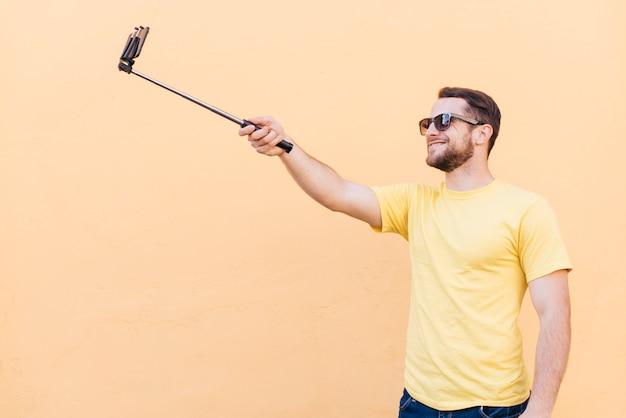 Hombre sonriente tomando selfie en teléfono celular de pie cerca de la pared de durazno