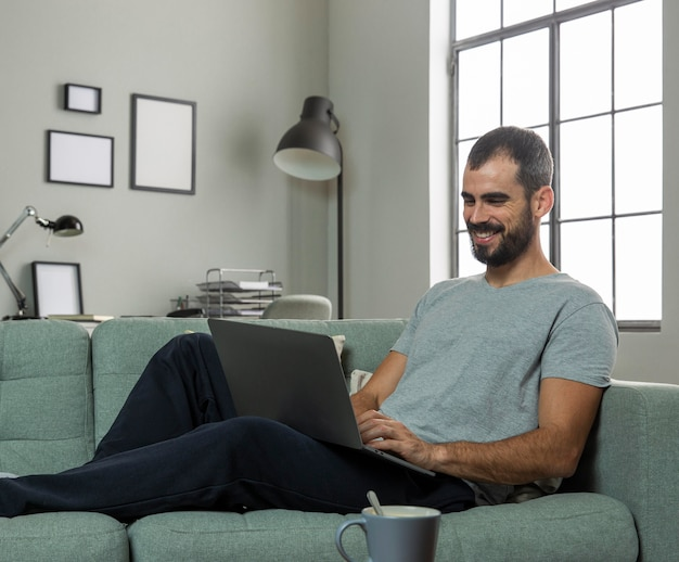 Hombre sonriente trabajando desde casa en portátil