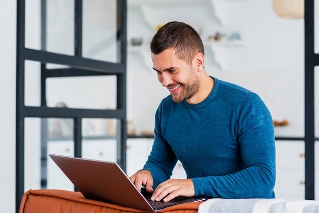 Hombre sonriente trabajando en la computadora portátil desde casa