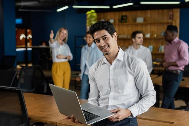 Hombre sonriente en el trabajo sosteniendo portátil y posando