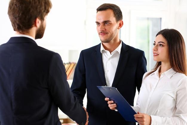 Hombre sonriente en traje se dan la mano como hola en la oficina