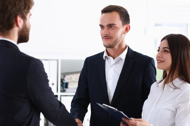 Hombre sonriente en traje se dan la mano como hola en retrato de oficina