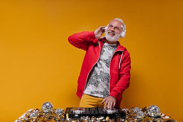 Hombre sonriente en traje elegante toca música con controlador de dj