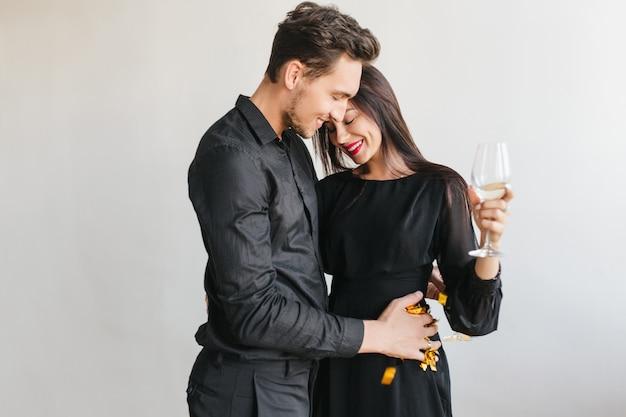 Hombre sonriente en traje negro sosteniendo confeti dorado y bailando con una mujer morena tímida