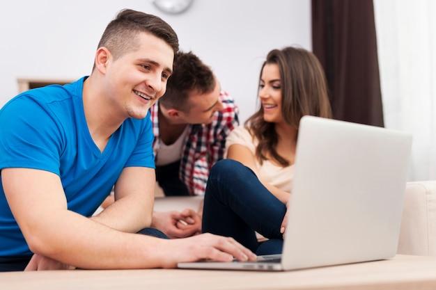 Hombre sonriente usando laptop con amigos en casa