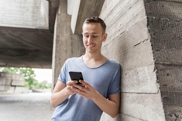 Hombre sonriente verificando móvil