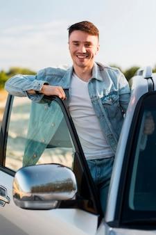 Hombre sonriente de vista frontal posando con coche