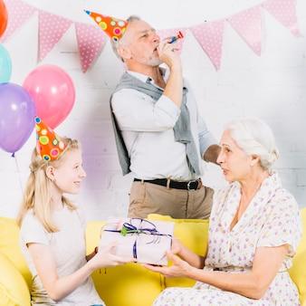 Hombre soplando una bocina de fiesta mientras una niña le da un regalo de cumpleaños a su abuela