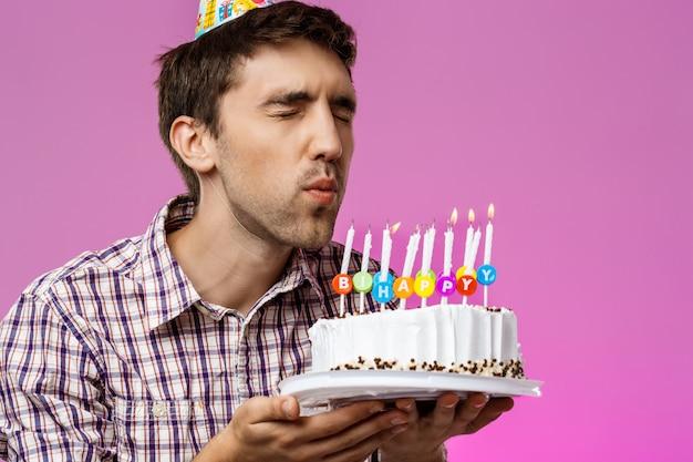 Hombre soplando velas en el pastel de cumpleaños sobre la pared púrpura.