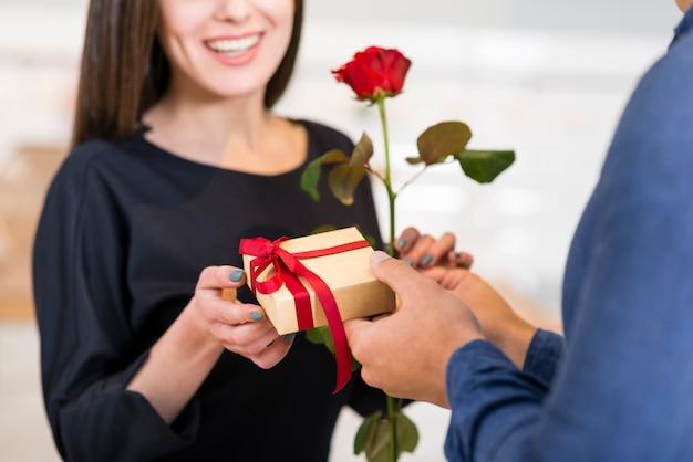 Hombre sorprende a su novia sonriente con un regalo de san valentín