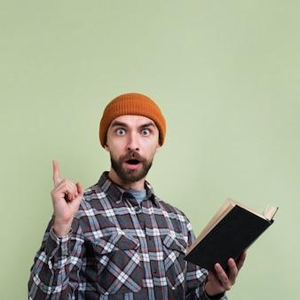 Hombre sorprendido apuntando el dedo hacia arriba