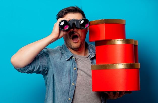 Hombre sorprendido con binoculares y regalos rojos