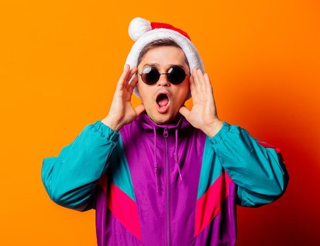 Hombre sorprendido en chándal de los 80 y gorro de navidad