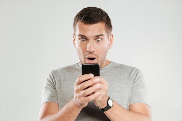 Hombre sorprendido chateando por teléfono móvil.