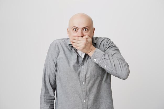 Hombre sorprendido cubre la boca y mira