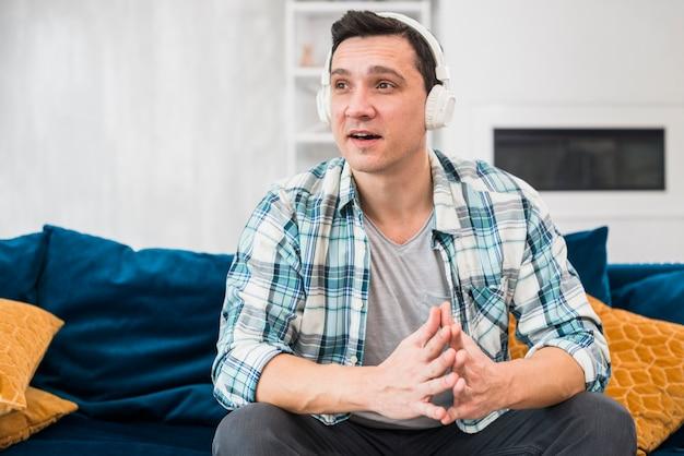 Hombre sorprendido escuchando música en auriculares en sofá
