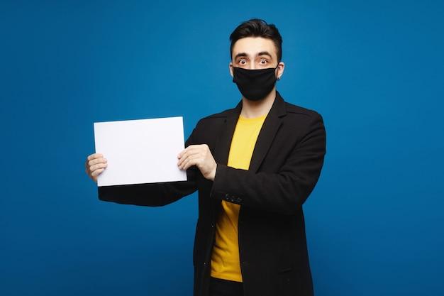Hombre sorprendido joven en una máscara protectora negra que sostiene una hoja de papel vacía y que mira en la cámara, aislada en el fondo azul. concepto de promoción. concepto de salud