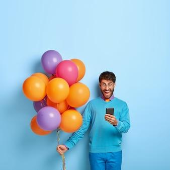 Hombre sorprendido lleno de alegría se centró en el dispositivo smartphone