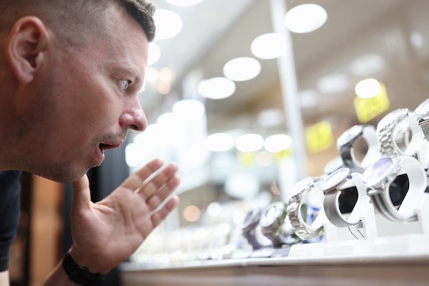 Hombre sorprendido mirando vitrina de cristal con reloj caro