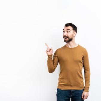Hombre sorprendido posando y apuntando hacia arriba