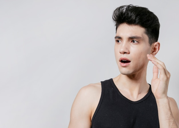 Hombre sorprendido posando en camiseta sin mangas