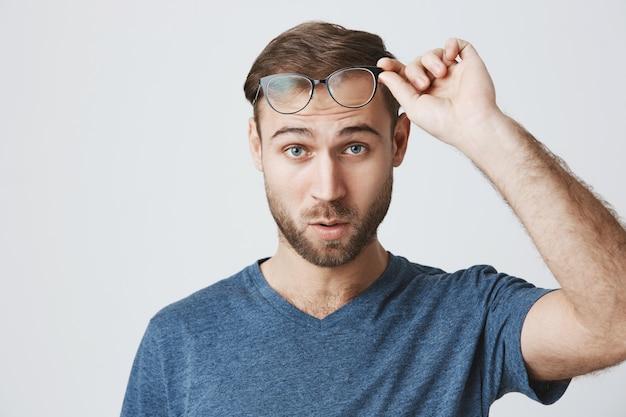 Hombre sorprendido quitarse los anteojos y mirar confundido