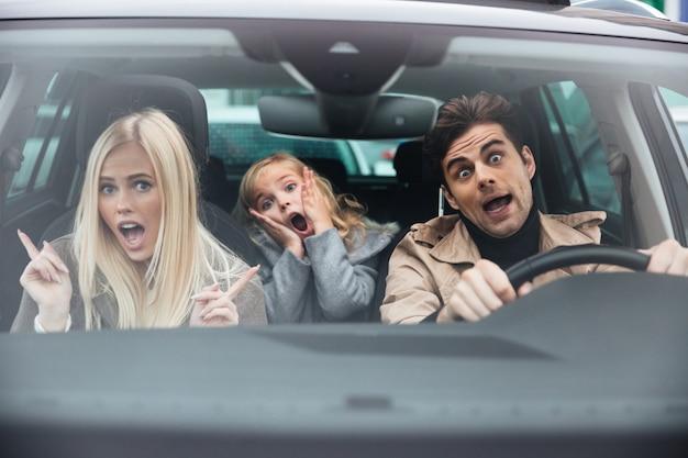 Hombre sorprendido sentado en auto con su esposa e hija