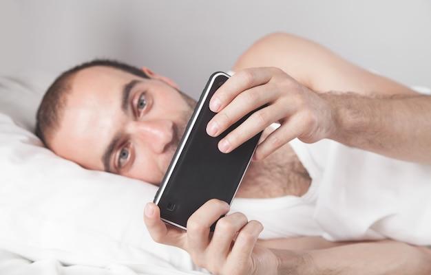Hombre sorprendido con smartphone en la cama.