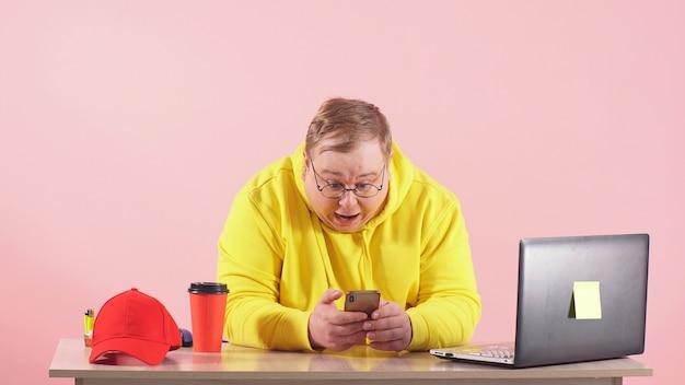 Hombre sorprendido y sorprendido en ropa deportiva amarilla está sentado en una mesa mirando las noticias sobre un fondo rosa en su teléfono inteligente