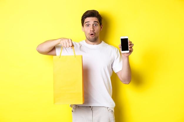 Hombre sorprendido sosteniendo la bolsa de compras y mostrando la pantalla del teléfono inteligente, concepto de banca móvil y logros de aplicaciones, fondo amarillo.