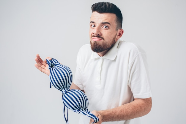 Hombre sorprendido sosteniendo un sujetador de mujer
