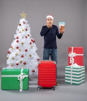 Hombre sorprendido sosteniendo sus boletos de viaje poniendo la mano sobre su rostro en gris