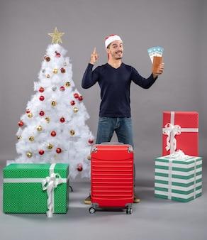 Hombre sorprendido sosteniendo sus boletos de viaje y señaló algo en gris