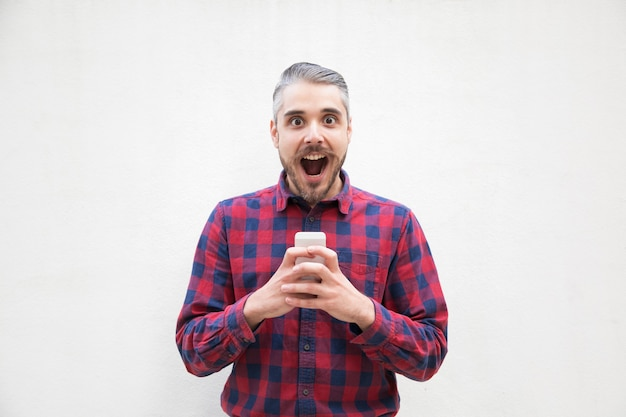 Hombre sorprendido con teléfono móvil mirando