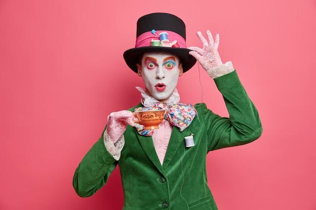 Hombre sorprendido tiene la imagen del misterioso sombrerero del país de las maravillas viste poses de maquillaje brillante con una taza de té vestido con ropa aristocrática aislada en una pared rosa
