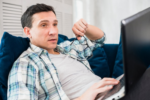 Hombre sorprendido usando laptop en sofá