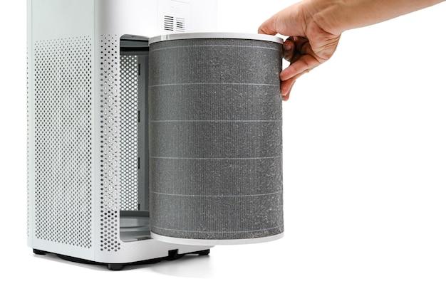 El hombre sostenga un filtro antiguo del purificador de aire, compruebe con filtro de cambio