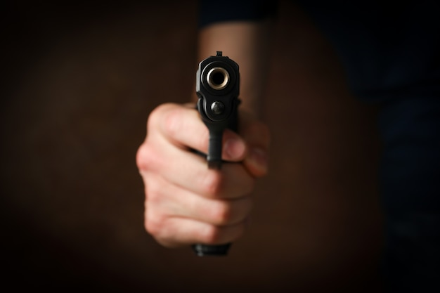 Hombre sostenga la pistola. enfoque selectivo. ladrón. violencia