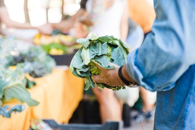 Hombre sosteniendo brassica romanesco mientras compra verduras en mercado
