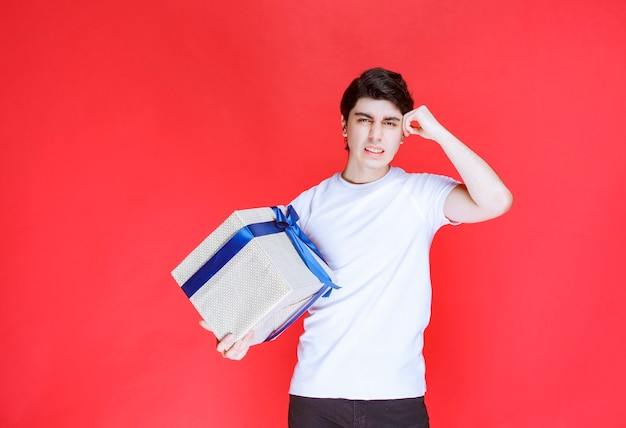 Hombre sosteniendo una caja de regalo azul blanca y pensando
