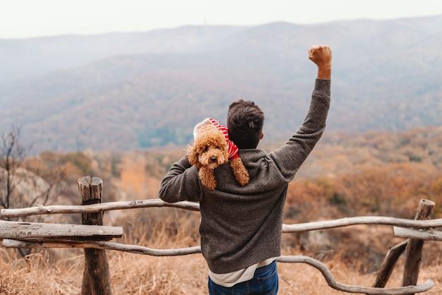 Hombre sosteniendo caniche sobre el hombro y levantando el puño en el aire. otoño. las espaldas se volvieron.