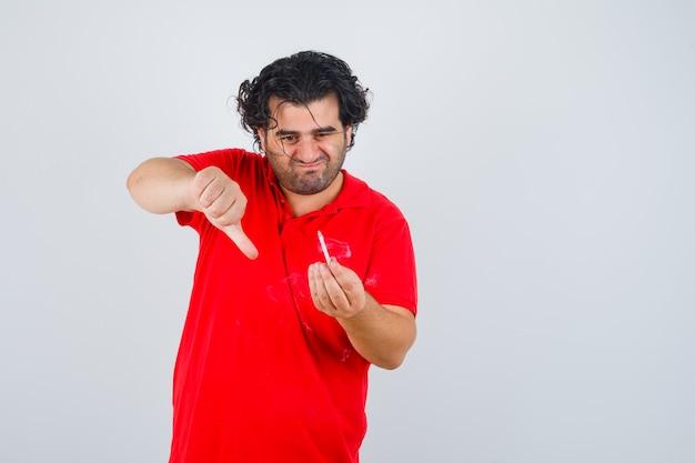 Hombre sosteniendo un cigarrillo, mostrando el pulgar hacia abajo en una camiseta roja y mirando enfocado, vista frontal.
