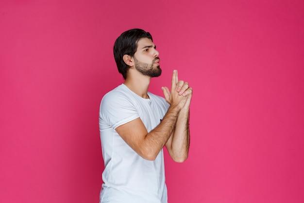 Hombre sosteniendo los dedos como una pistola.