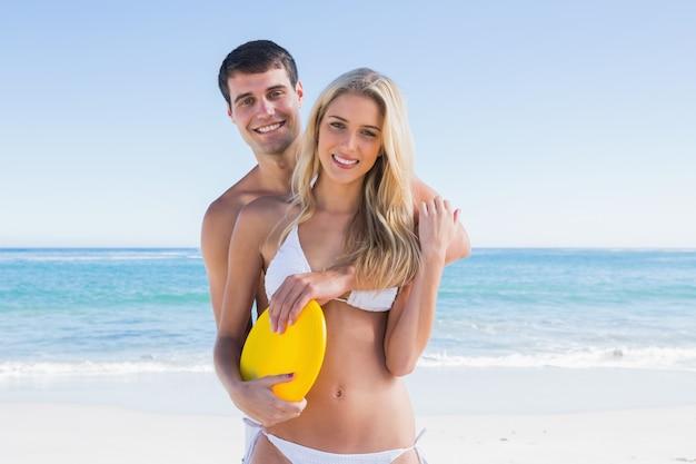 Hombre sosteniendo un disco volador y abrazando a su novia