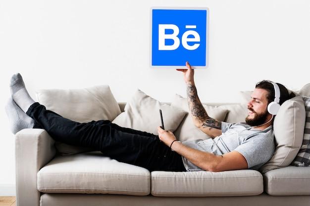 Hombre sosteniendo un icono de behance en el sofá